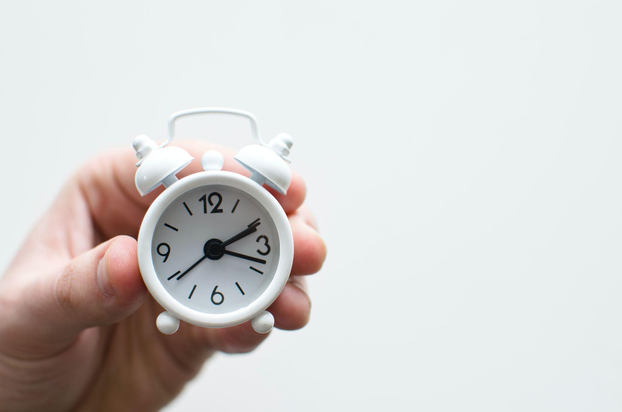 hand holding analog clock