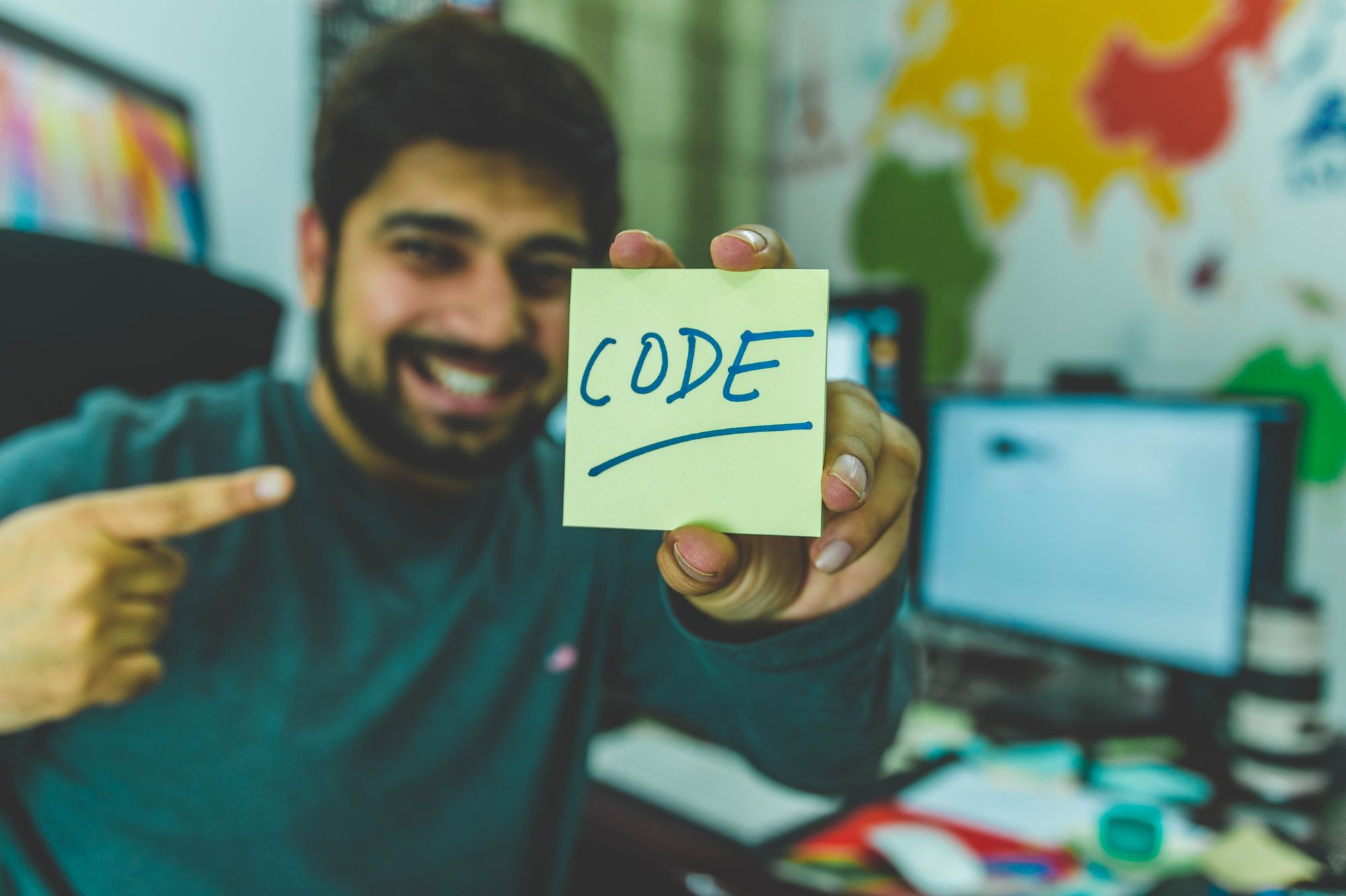 Man showing note with the word written code