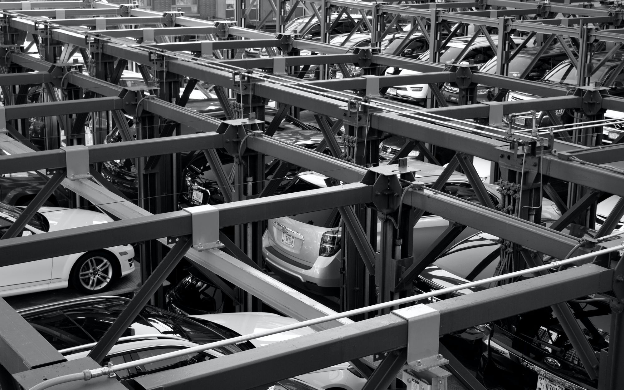 Top angle view of a vehicle assembly line in black and white.
